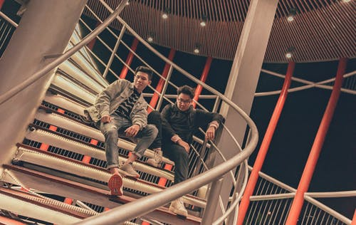 Two Men Sitting on Spiral Stairway