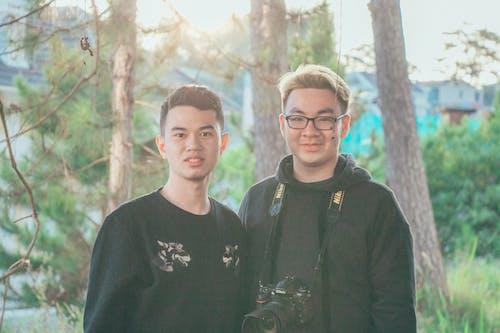 木の幹の近くに立っている2人の男性