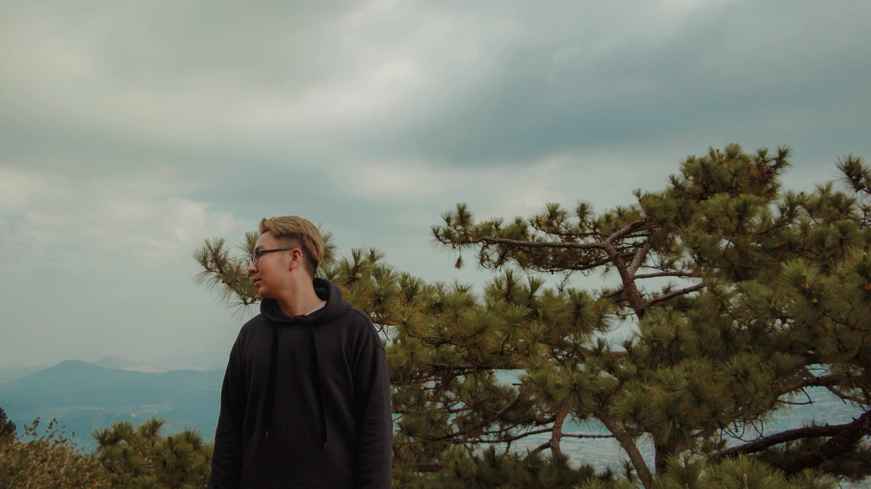 Man in Black Hoodie Standing Near Green Leaf Tree