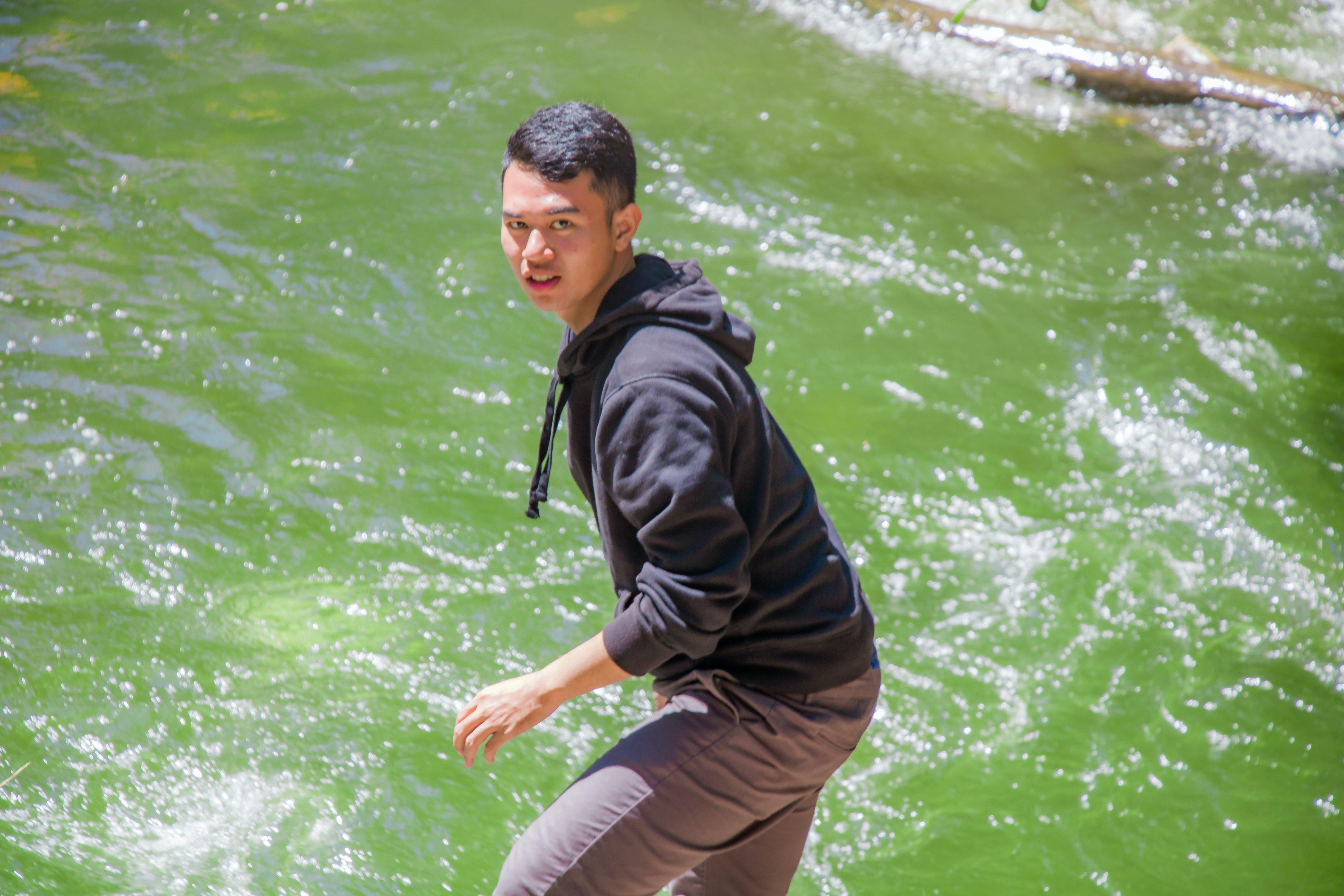 Man in Black Hoodie Standing in Front of Body of Water