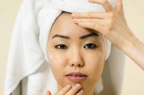 Woman putting cosmetic product on her face