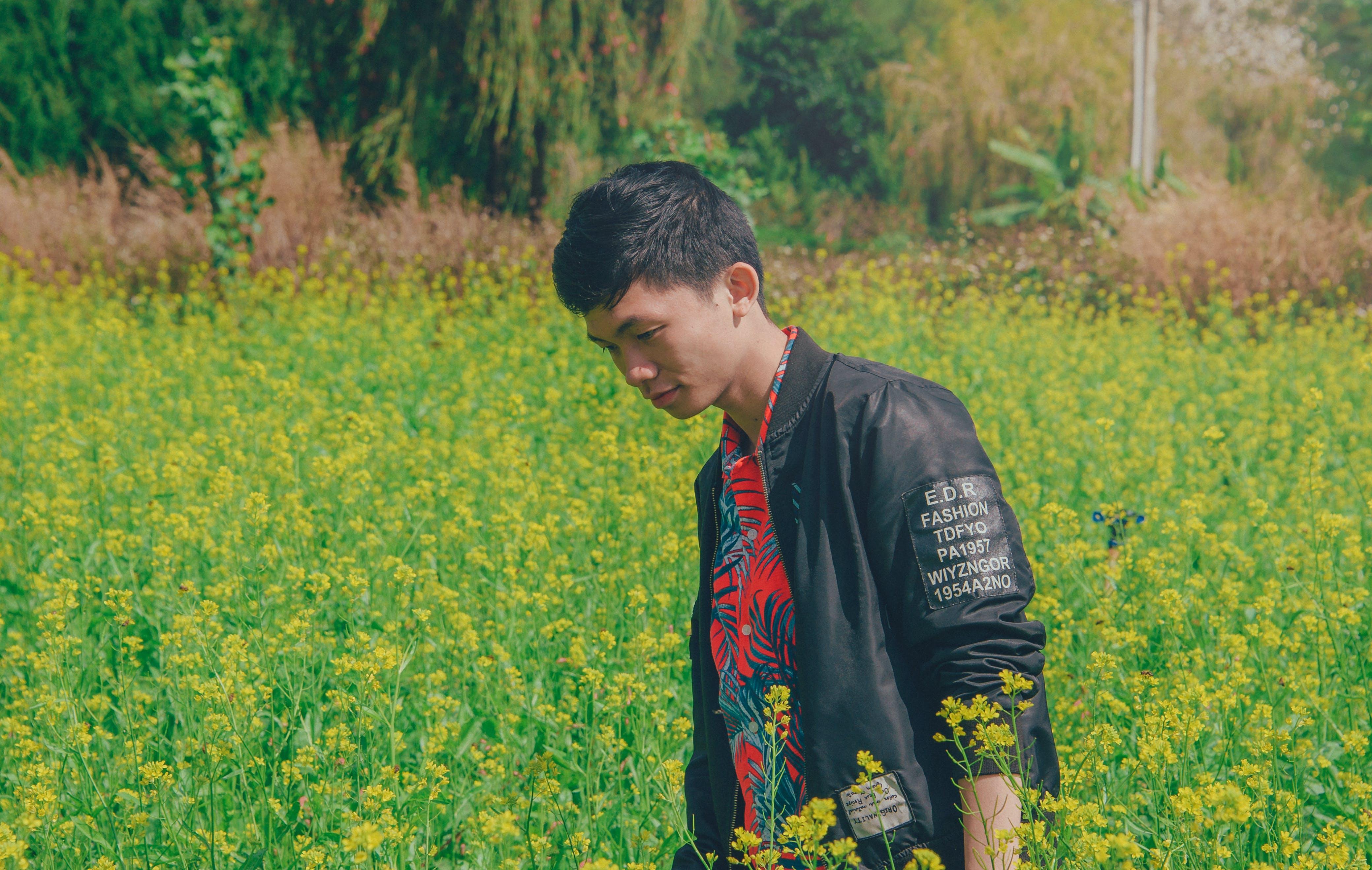 Man Wearing Black Jacket on Yellow Flowers