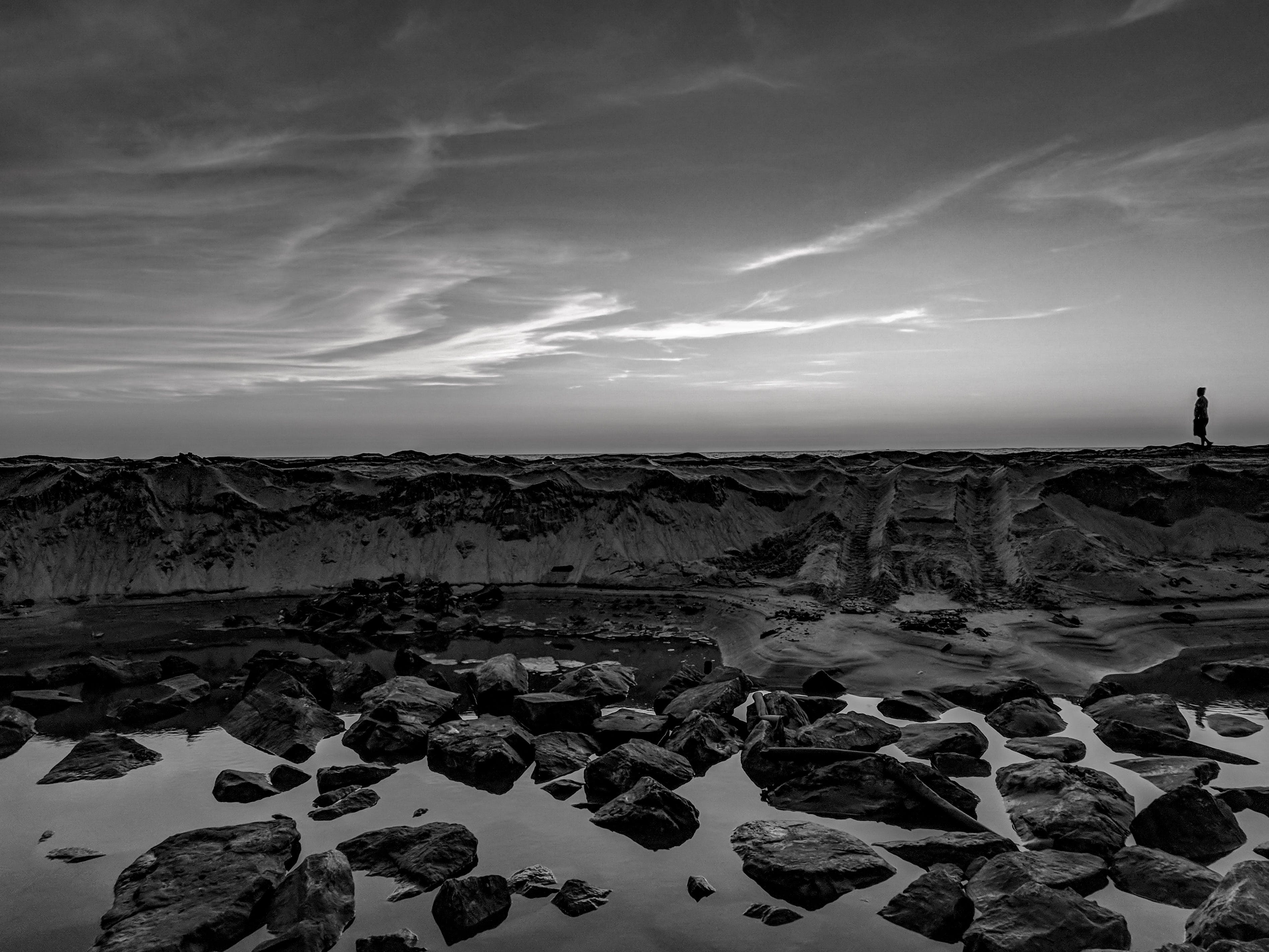 Grayscale Photo Of Person Walking On Rocks