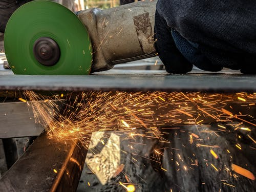 Person Using Green And Grey Angle Grinder On Sheet Of Metal
