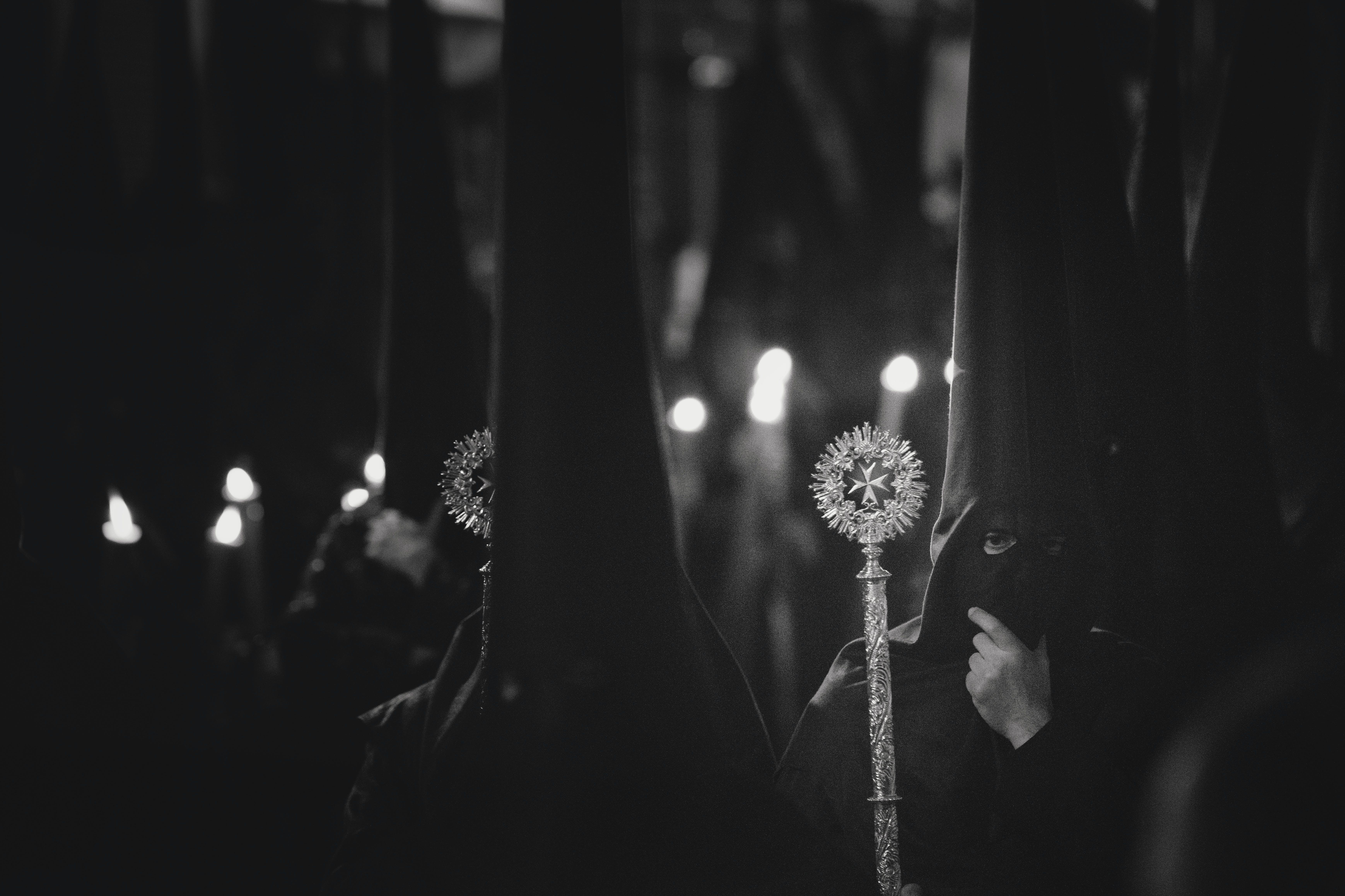 Grayscale Photo of Person Wearing Balaclava Holding Wand