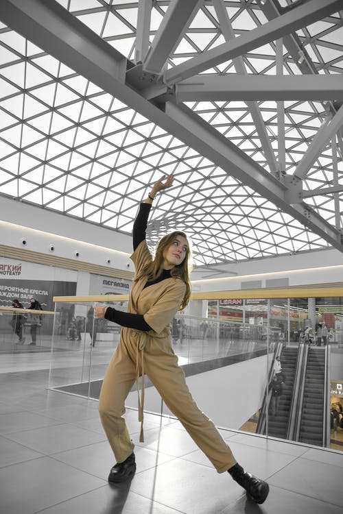 Woman in Brown Long Sleeve Shirt and Beige Pants Standing on White Floor Tiles