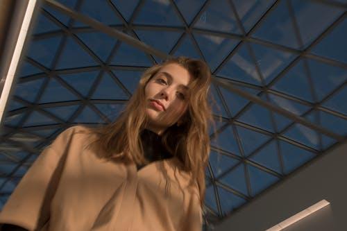Woman in Beige Long Sleeve Shirt Standing Near Blue Metal Frame