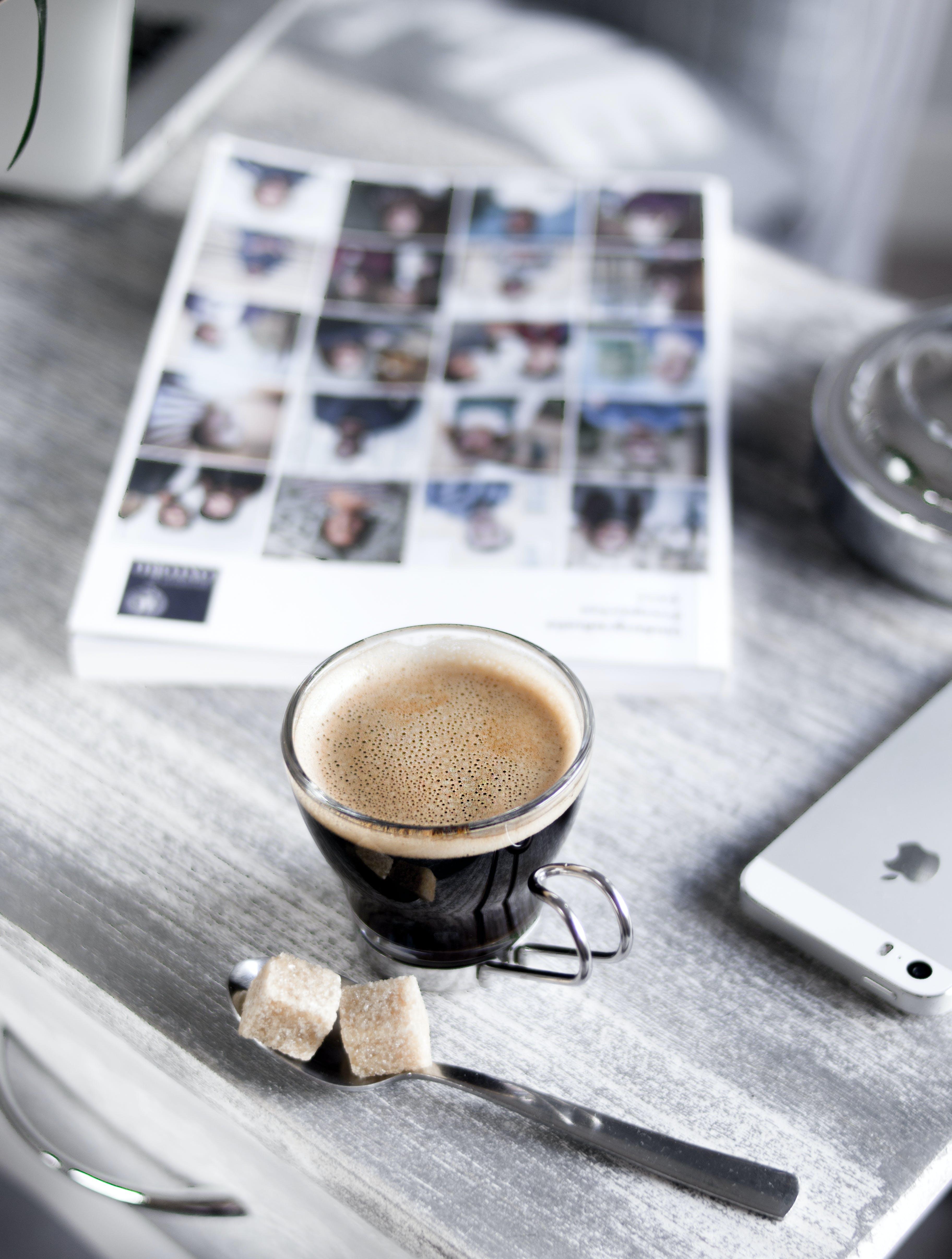 Darmowe zdjęcie z galerii z biurko, czarna kawa, czasopismo, drewniane biurko