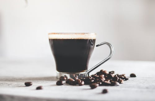 Aromatic black coffee in glass cup with metal handle and scattered coffee beans on light wooden table against blurred background