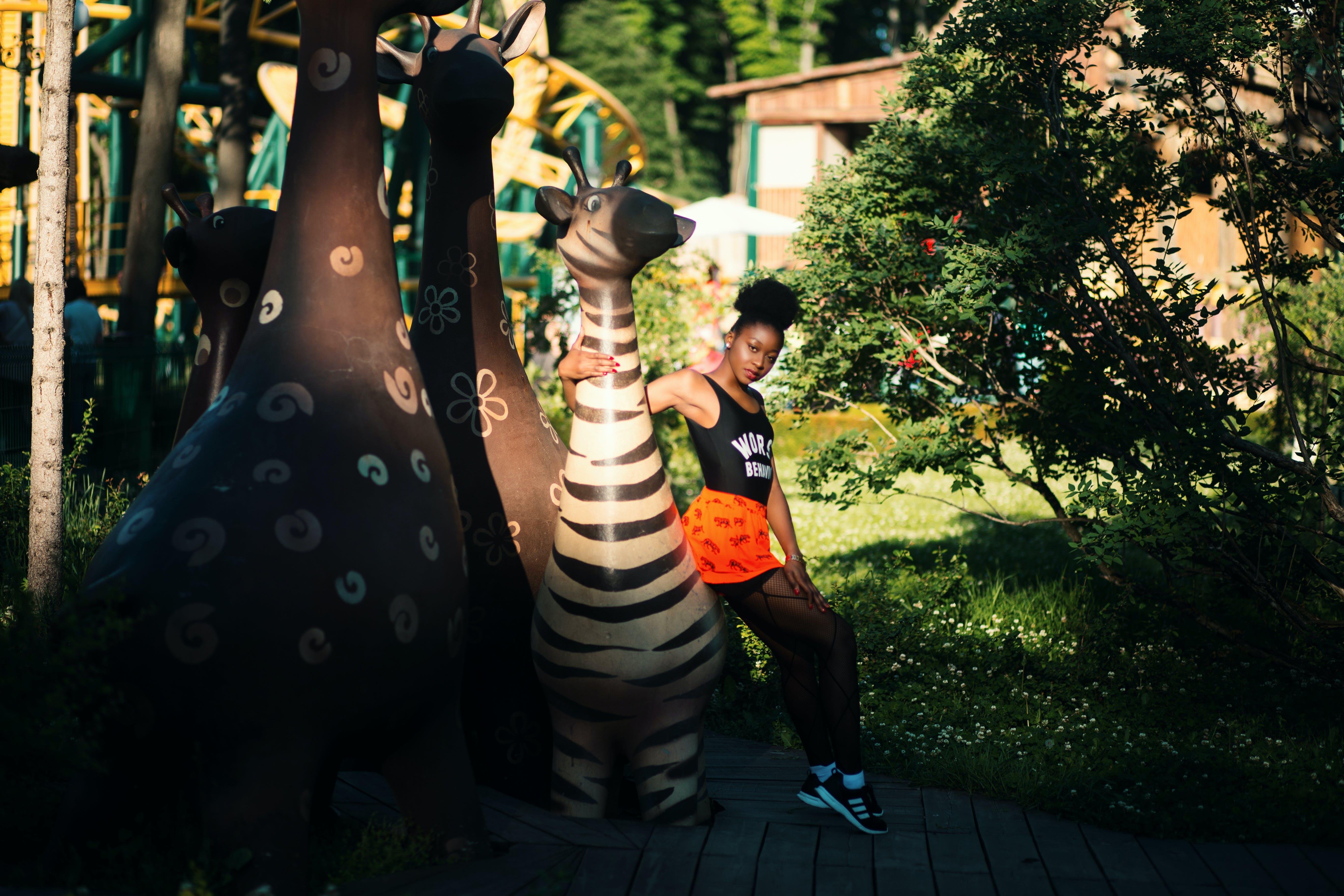 Photo of Woman Sitting on Zebra Statue