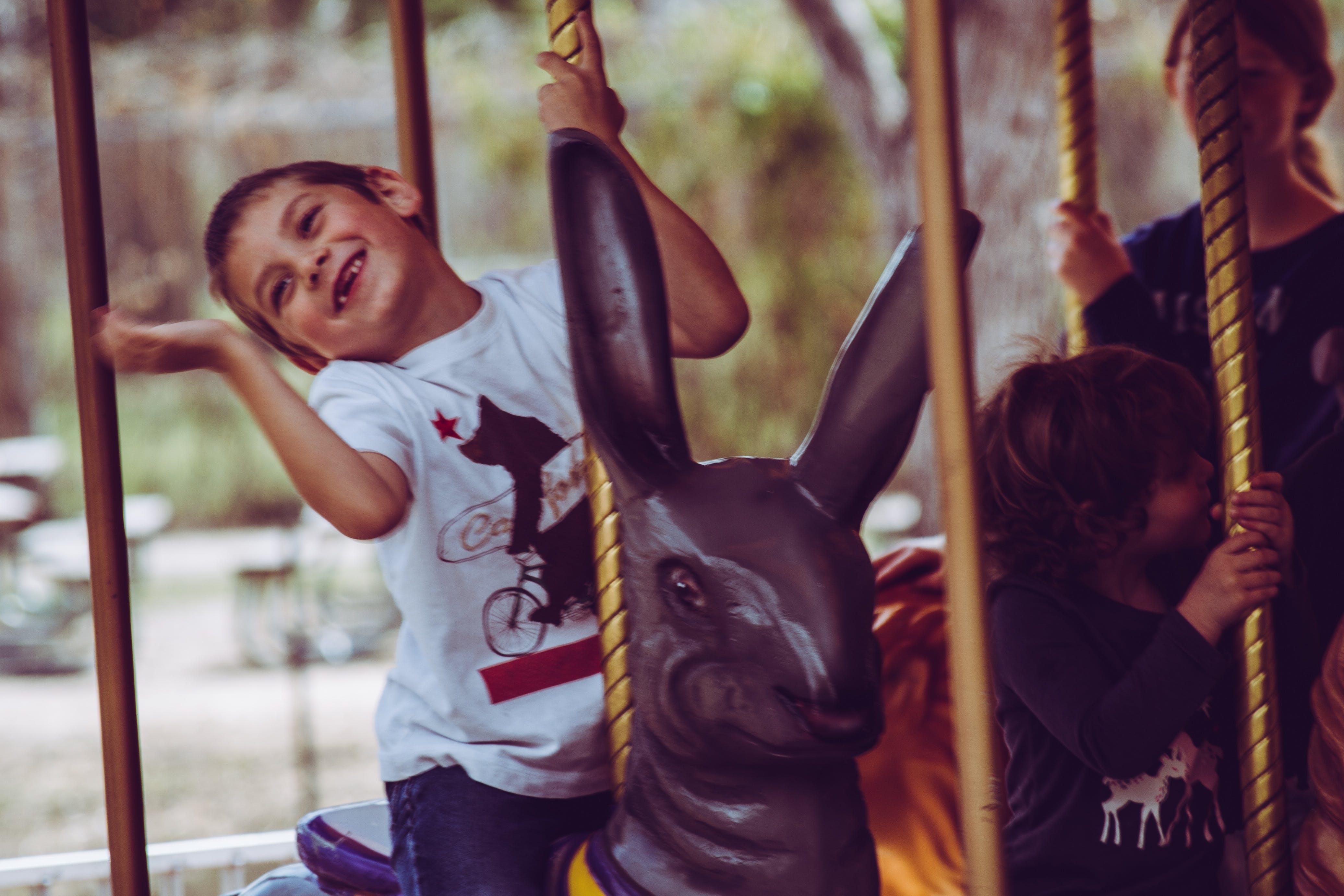 Boy in White T-shirt Riding Carousel