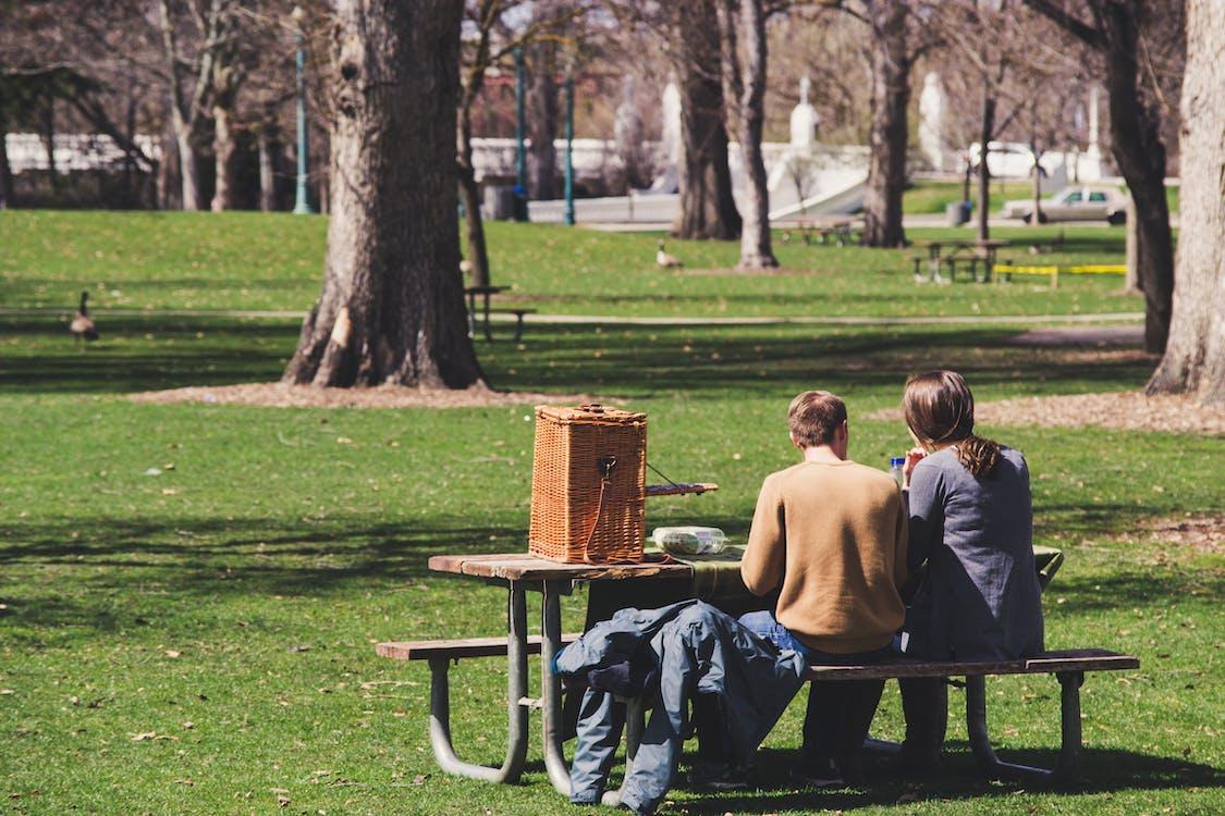 茶色の木製のピクニックテーブルに座っている男性と女性