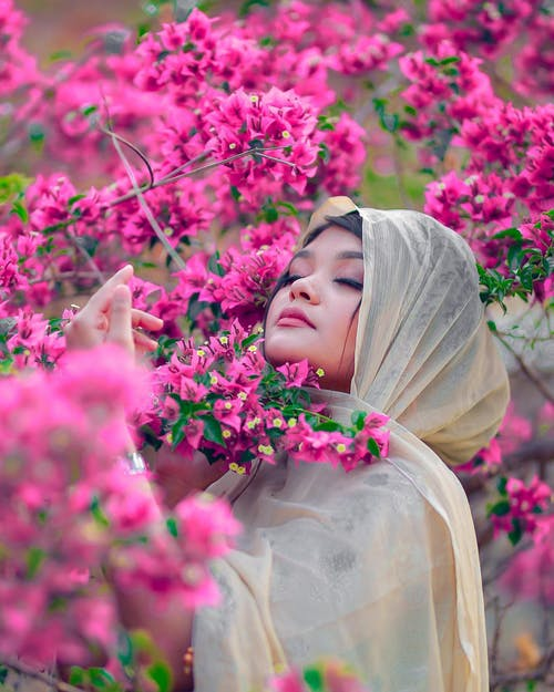 Woman in White Hijab Holding Pink Flowers