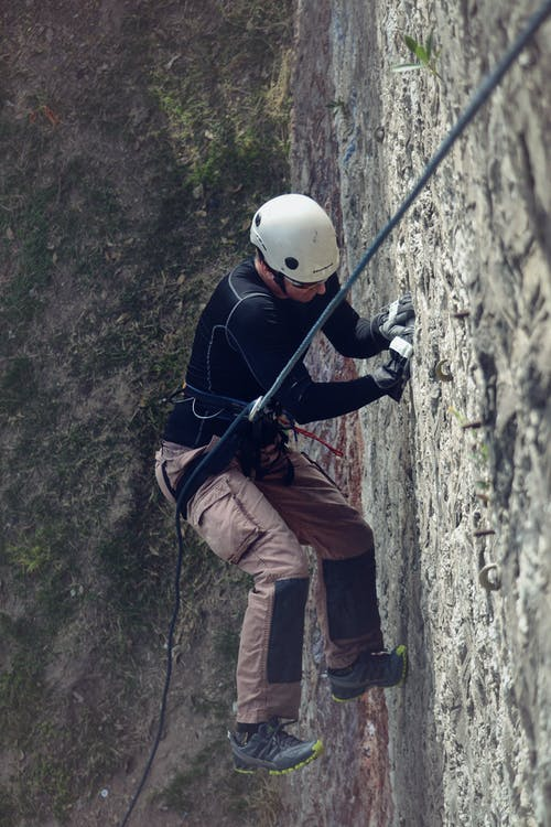 Person in White Hard Hat Climbing Wall