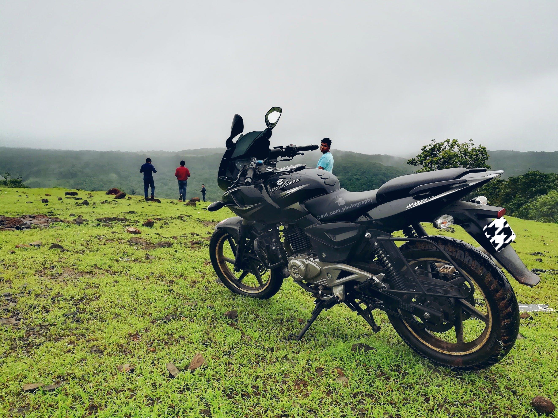 Black Backbone Motorcycle Near Man in Blue Shirt at Daytime