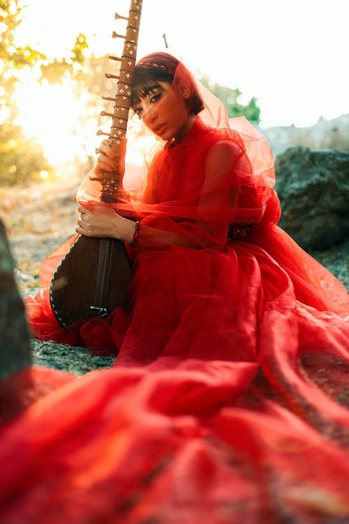 Farsi woman in red dress sitting on ground holding traditional instrument
