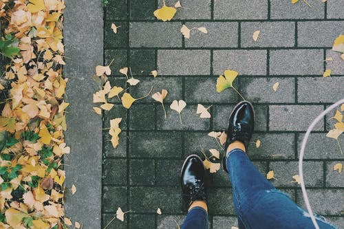 Person Wearing Black Patent Leather Dress Shoes on Gray Brick Pathway