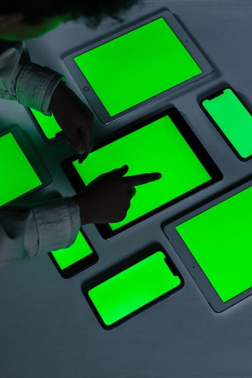 Blackskined boy touching iPad with green screen
