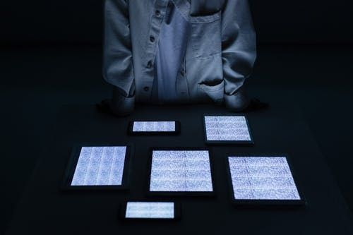 Person standing at table with tablets and smart phones