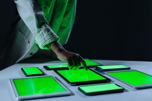 Human hand touching iPad with green screen