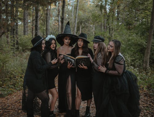 Group of women dressedas witch coven reading spell book in forest