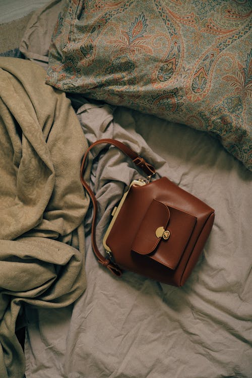 Small brown leather bag on bed