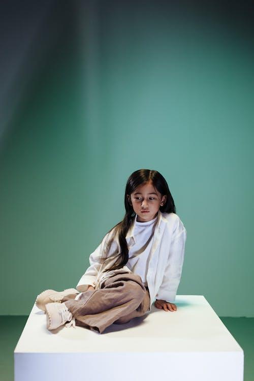 Teenage girl sitting on white podium