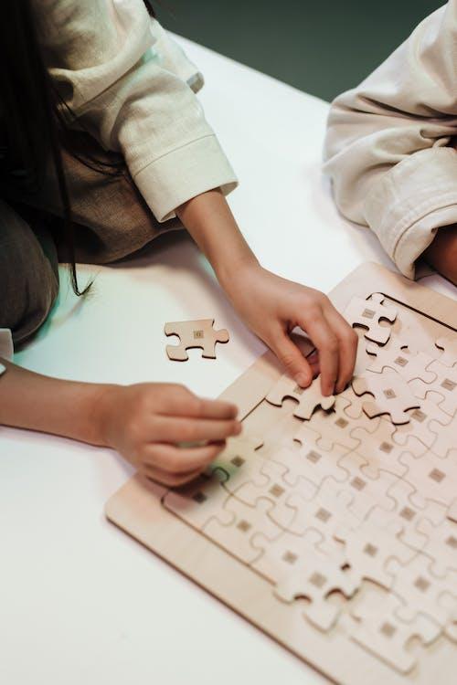 Unrecognizable hands doing jigsaw puzzle