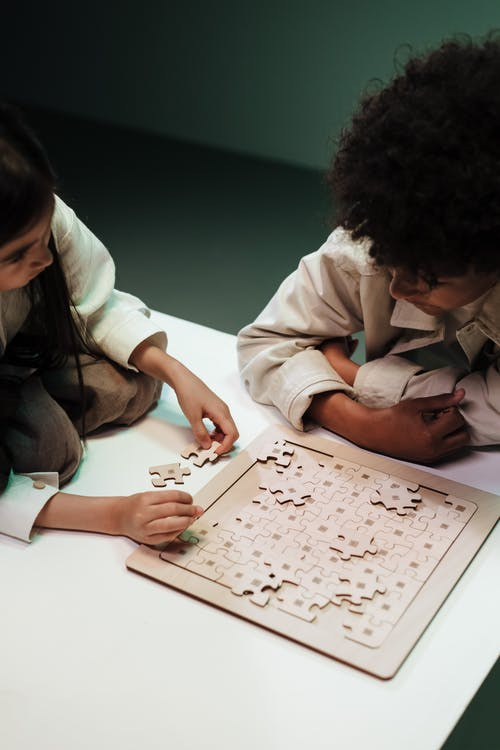 Children adjusting elements of jigsaw puzzles