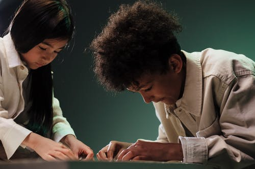Two teenagers doing jigsaw puzzle