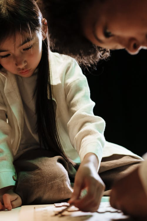Teenage girl kneeling on table and doing puzzles with her big brother