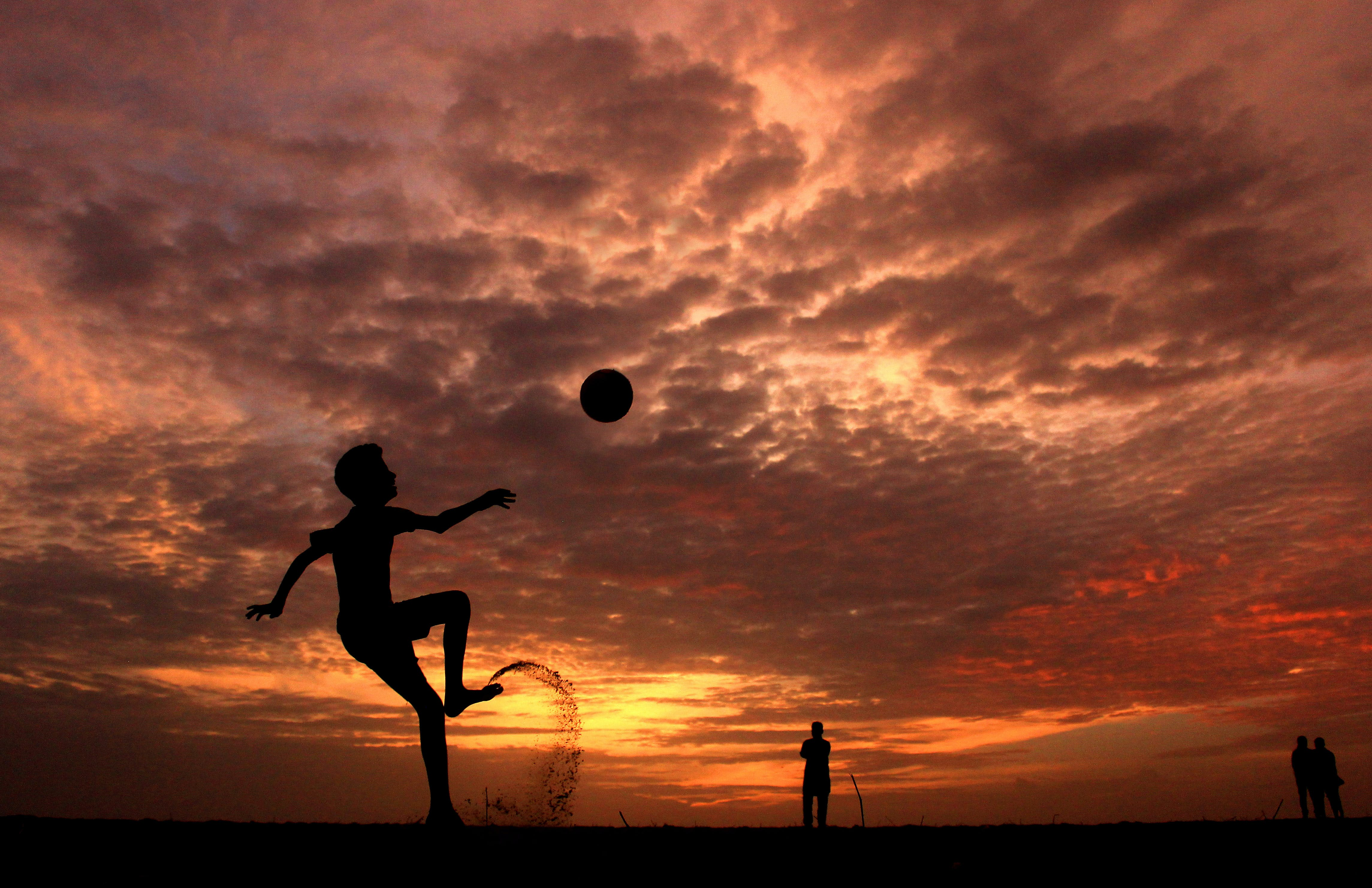 Silhouette of a Boy Playing Ball during Sunset