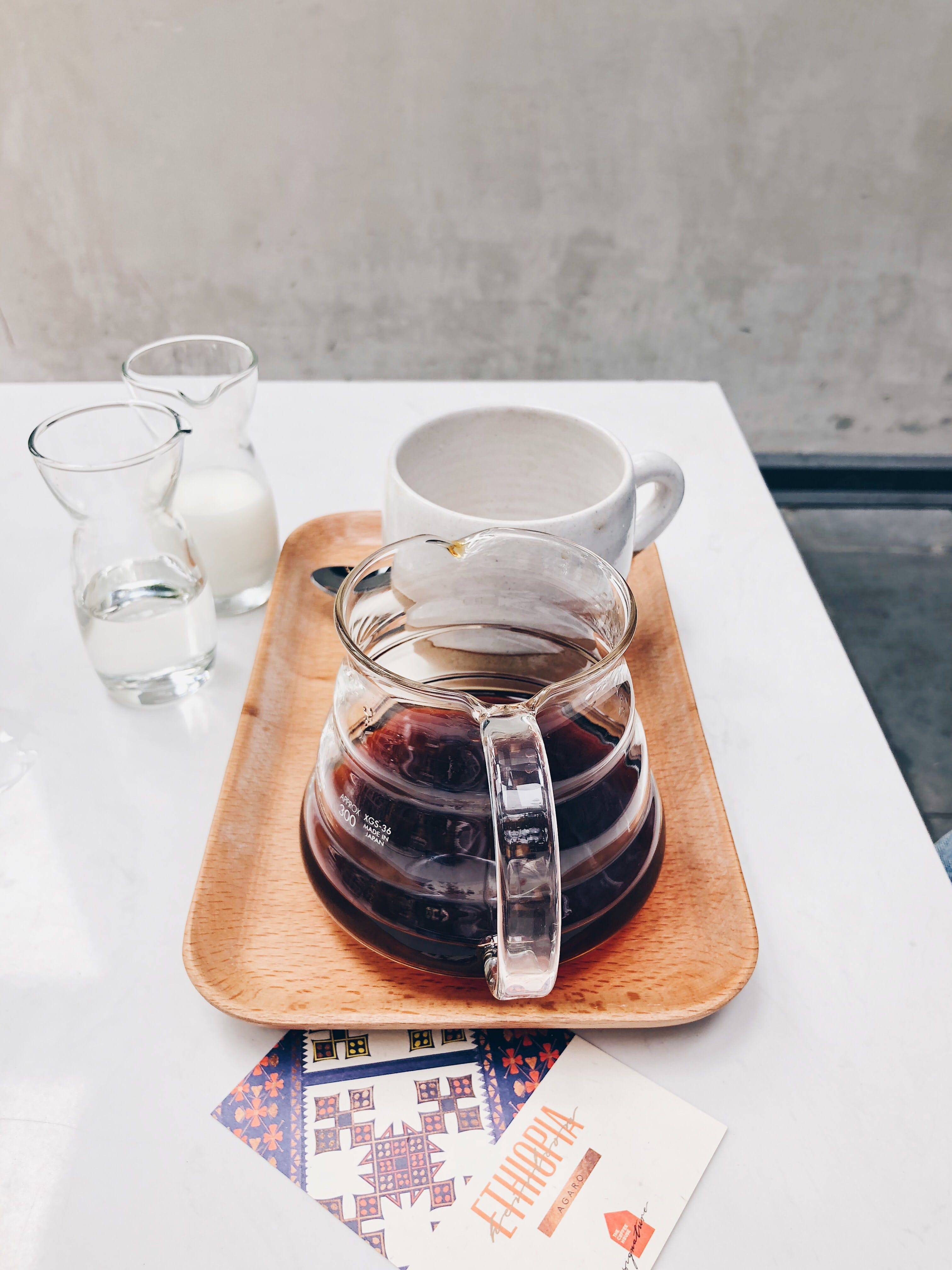 Clear Glass Coffee Pot Near White Mug on Brown Tray