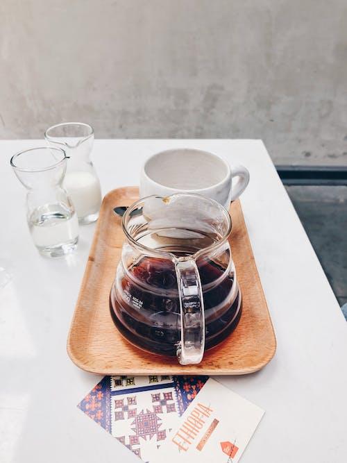 Clear Glass Coffee Pot Near White Mug on Brown Tray
