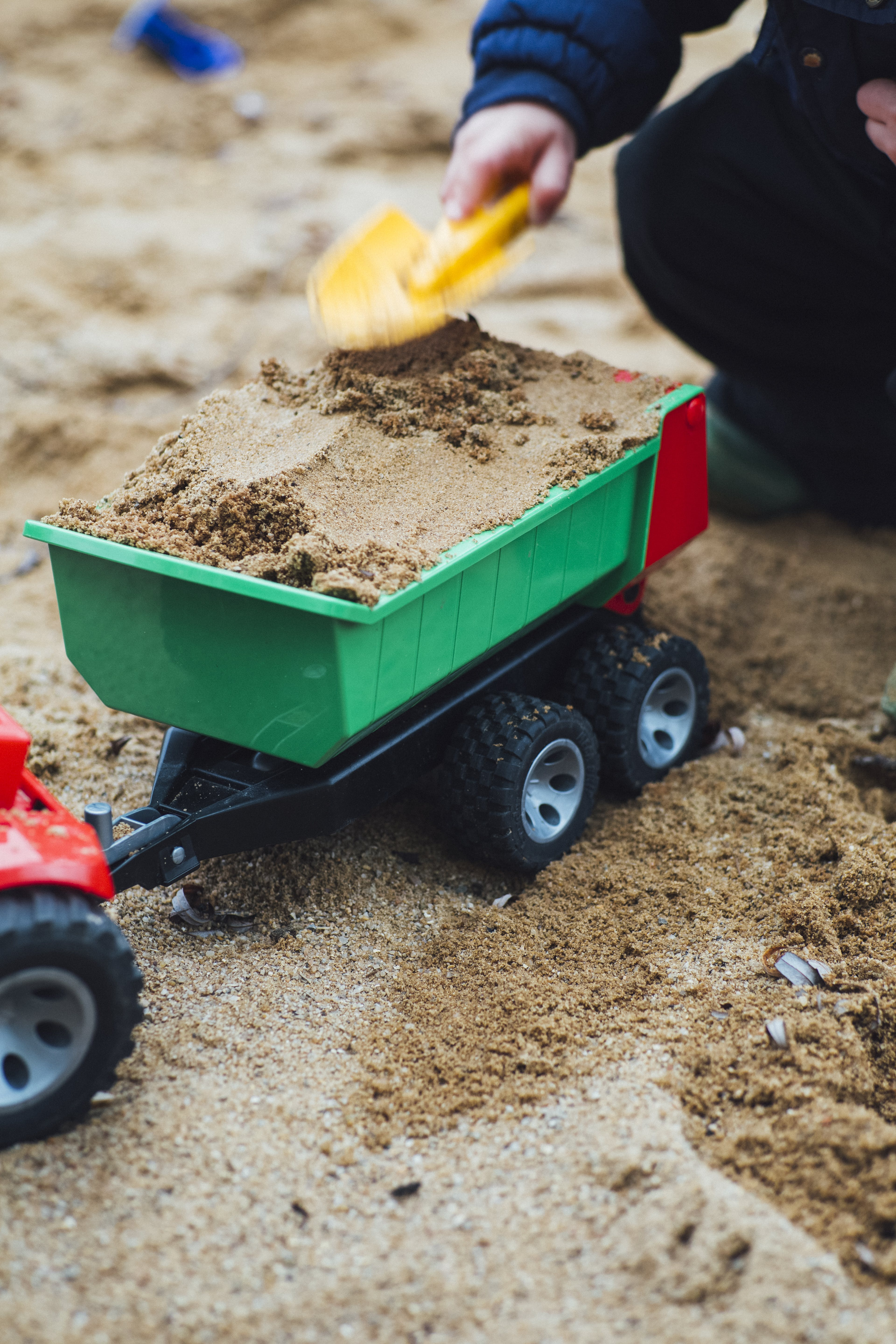 Child Playing Sand With Shovel and Truck Toy