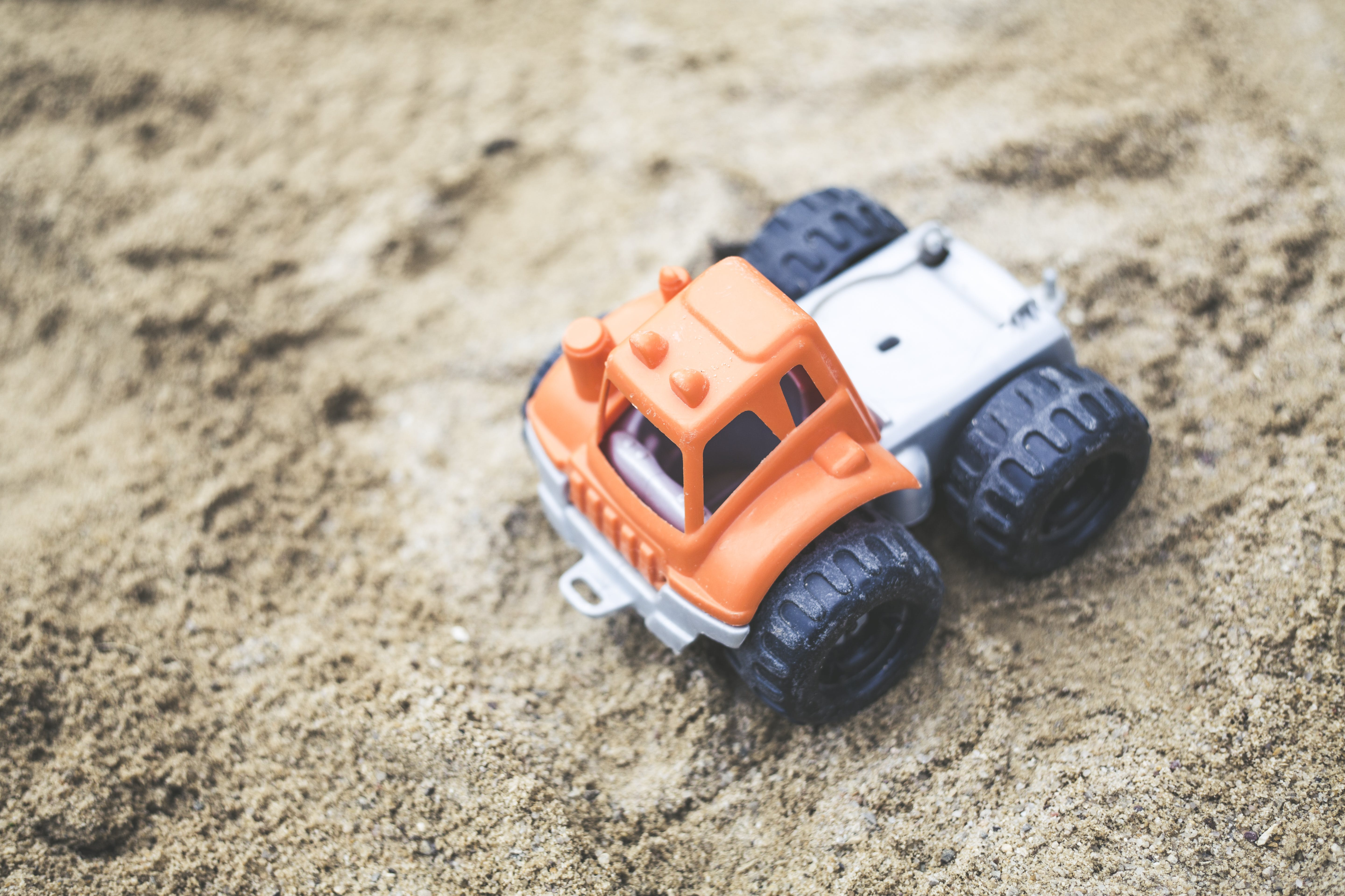 Orange and Gray Plastic Truck Toy on Sand