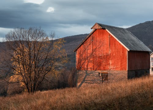 Brown Wooden Barn on Brown Grass Field Under Gray Cloudy Sky