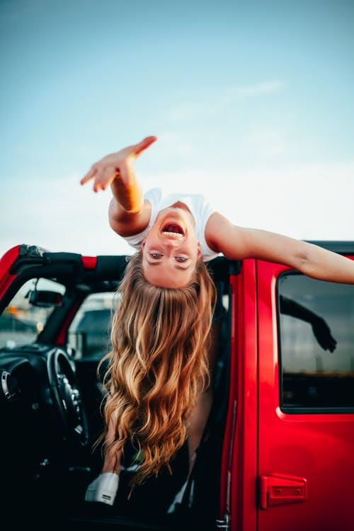 Girl laying on car roof reaching out smiling