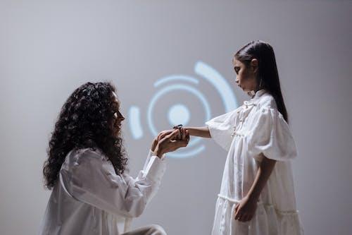 Kneeling mother holding daughters hand