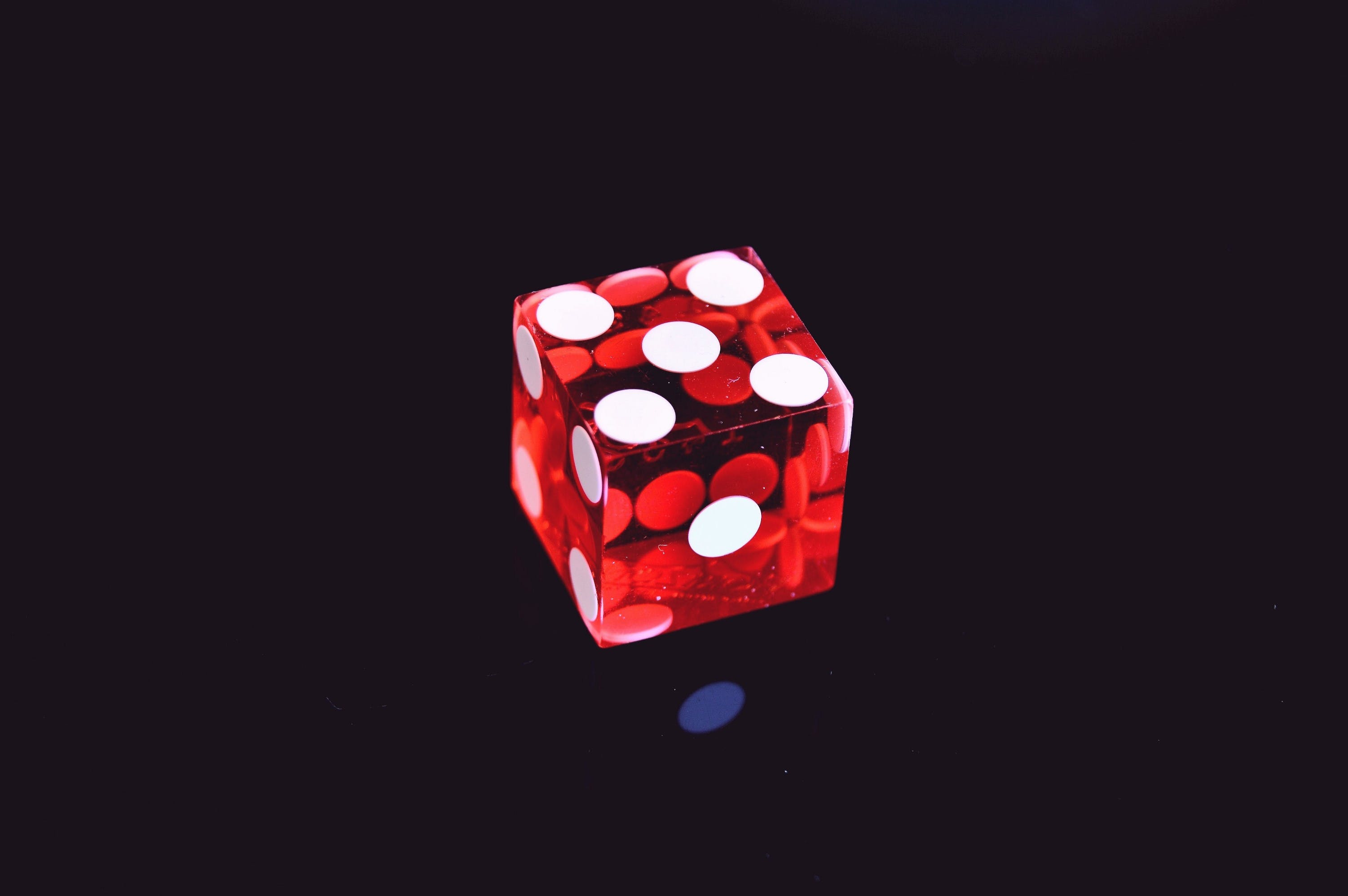 Red Translucent Die on Top of Black Surface