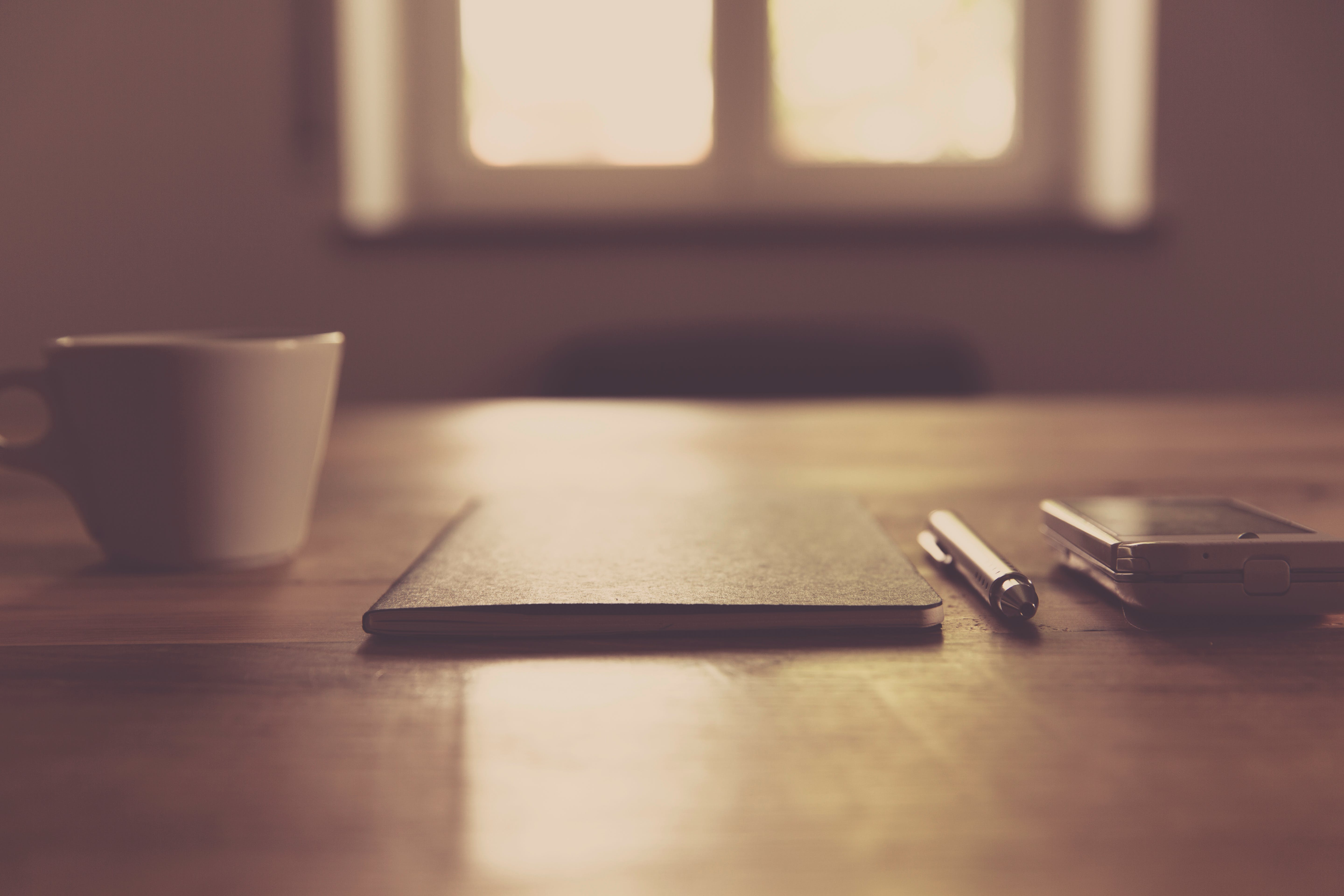 Black Closed Notebook Beside Click Pen and White Cup