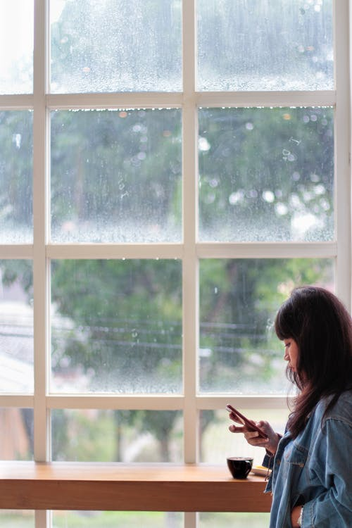 Woman Wearing Blue Denim Jacket Holding Smartphone Standing Beside Clear Glass Window