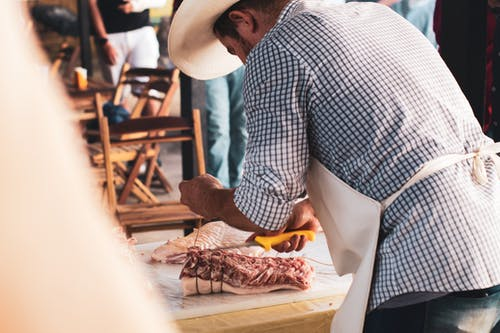 Man in Blue and White Checkered Dress Shirt Slicing Meat