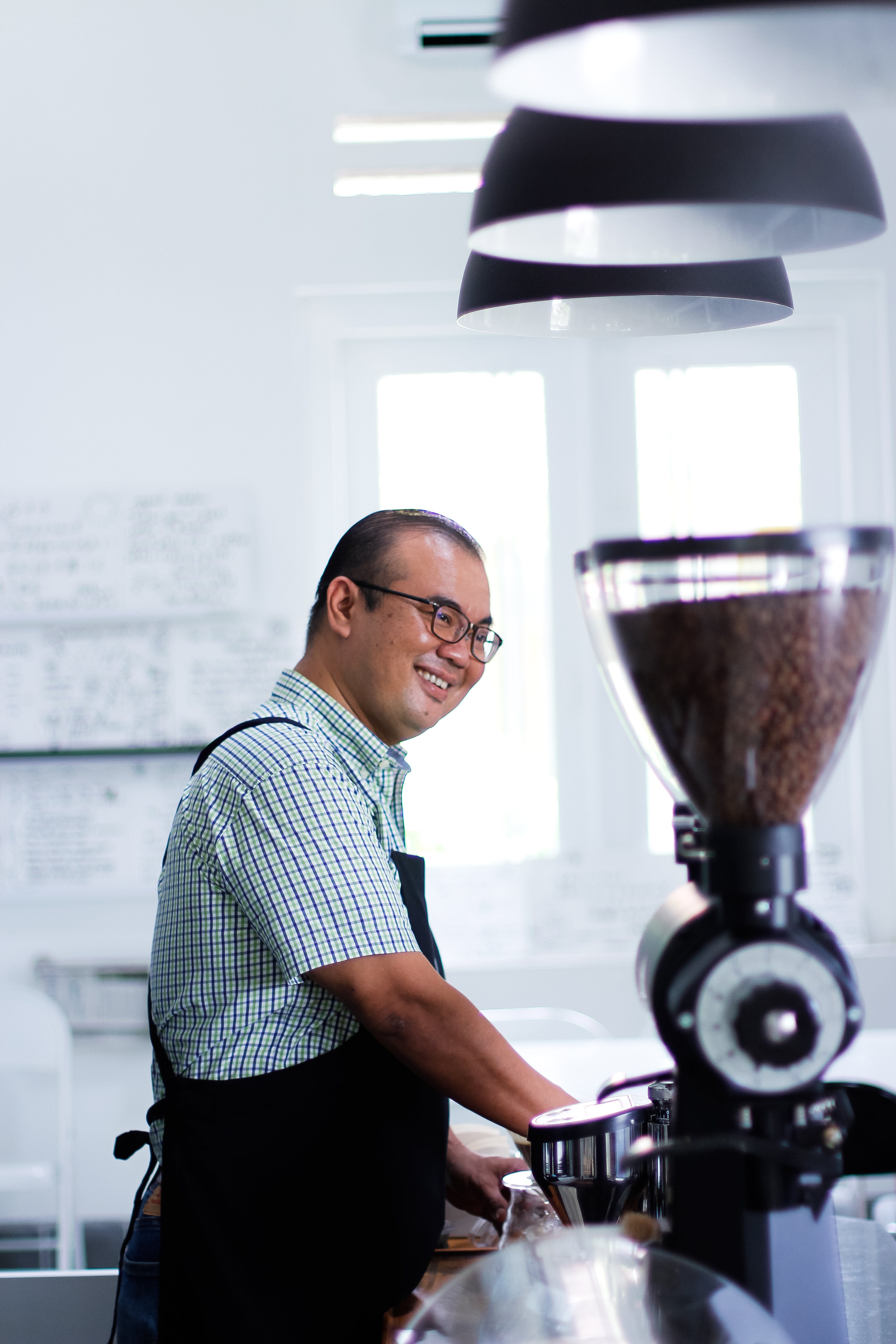 Man Wearing Plaid T-shirt And Black Apron in Front of Coffeemaker