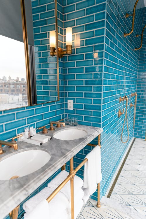 White Ceramic Sink Near Blue Wall Tiles