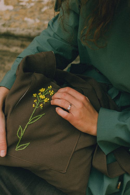 Womans hands holding olive colour textile bag with embroidered yellow flower