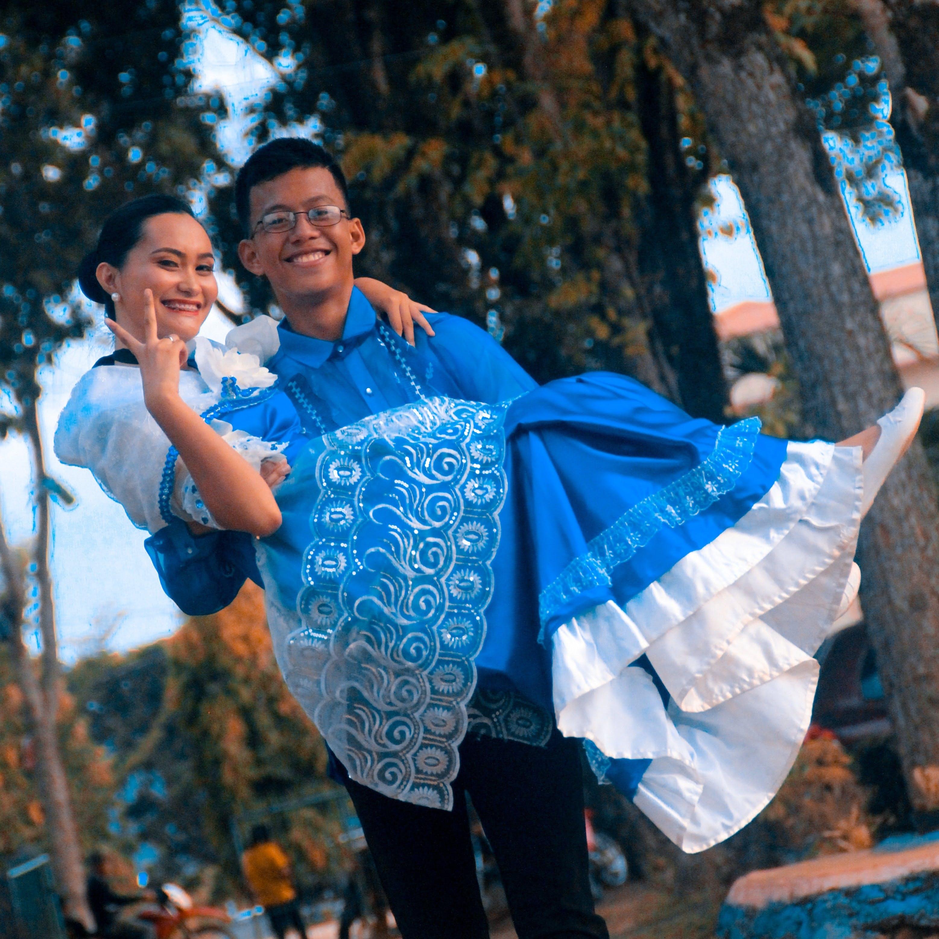 Man Wearing Blue Button-up Shirt Carrying Woman