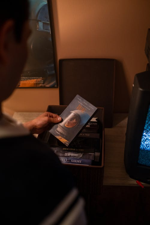 Man browsing VHS movies collection