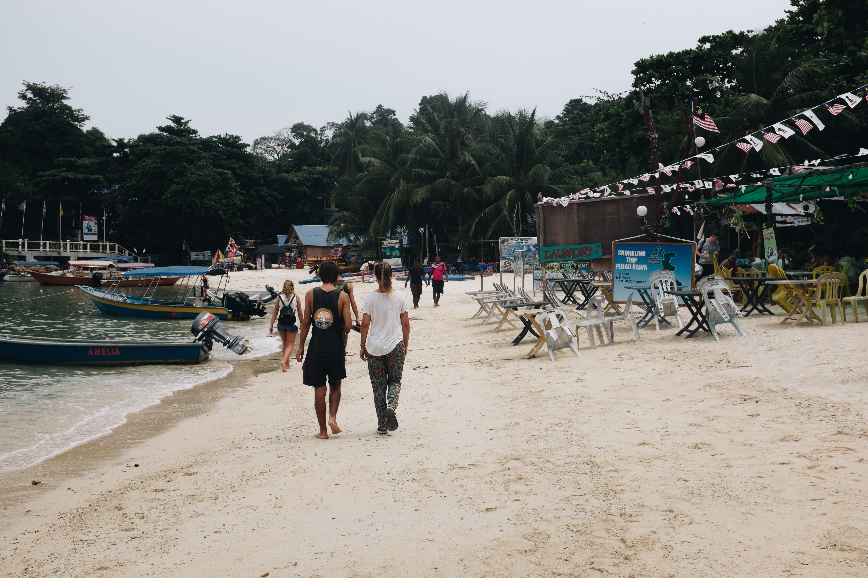 Group of People Walking on Seashore