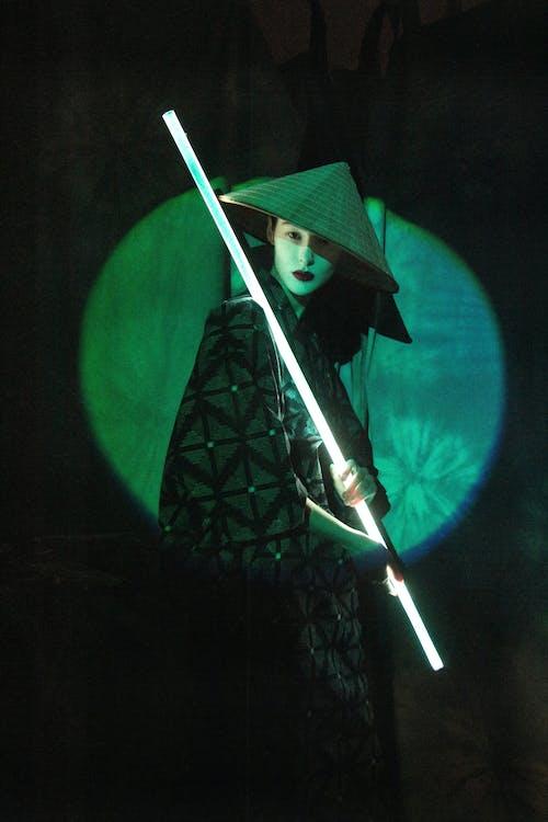 An Asian actress holding a light stick and looking at camera